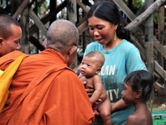 bonze avec bébé cambodgien au village lacustre de Kompong Khleang