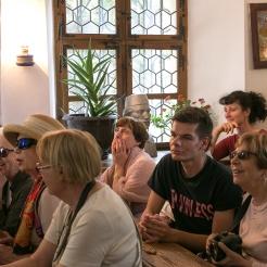 assis dans la plus ancienne classe roumaine, à l'écoute d'un prêtre orthodoxe, expert des archives locales.