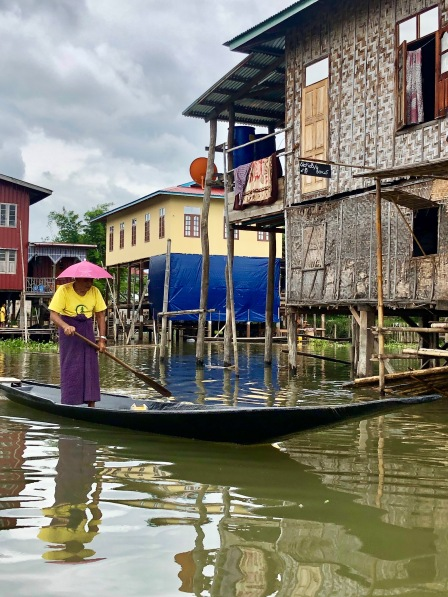 Birmane en train de ramer avec un chapeau rose avec maison sur pilotis au lac inle