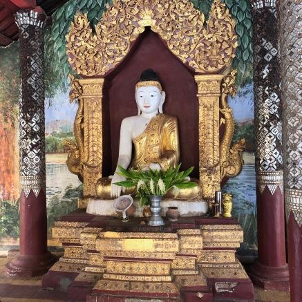 Bouddha en tailleur fait de pierre blanche et d_une toge dorée. Des offrandes sont devant lui