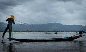 photo horizontale d_un pécheur sur le lac Inle relevant son filet
